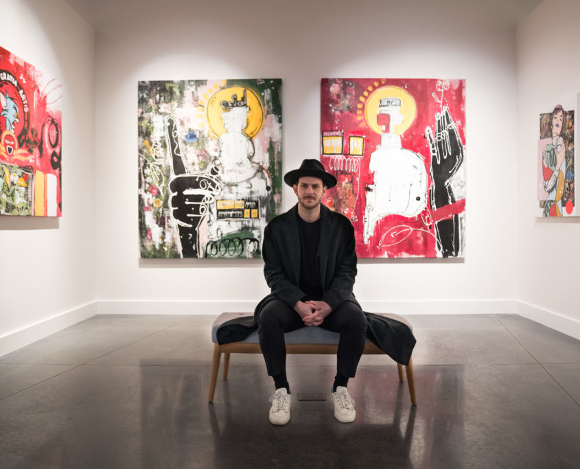Artist Felipe Echeverry known as LaSso seated in front of his paintings, 2019. Courtesy Avant Gallery.